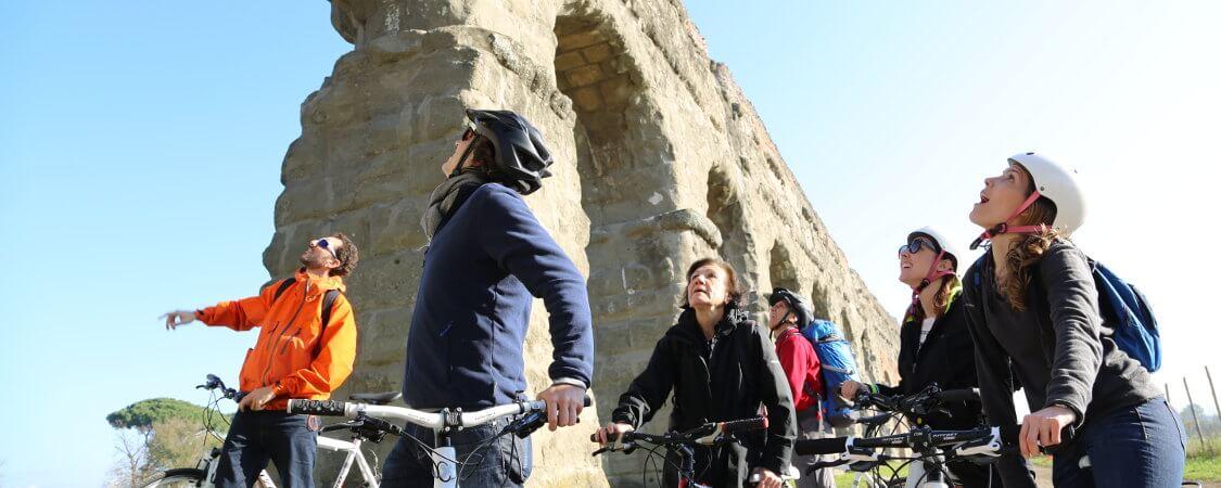 Eine Gruppe Radfahrer stoppt unter einem Aquädukt