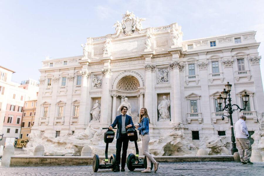Couple souriant et leur Segway posant devant la fontaine de Trevi.