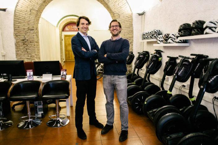Die Rex-Tours Gründer Leo und Massi im Büro von Rex-Tours, umgeben von Segways und Fahrrädern.