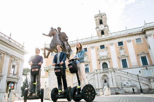 Drei Freunde auf Segways auf dem Kapitolinischen Hügel vor der Statue des Marc Aurel
