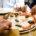 Eine Nahaufnahme eines gedeckten Tisches, vier Hände greifen um Stücke einer Pizza Margherita
