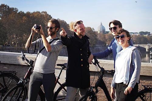 Eine Gruppe genießt den Ausblick von der Ponte Sisto, im Hintergrund der Petersdom